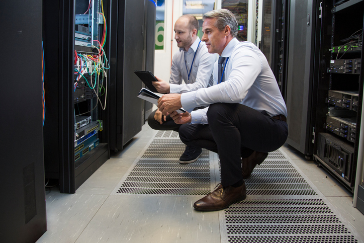 Computer technicians holding digital tablet while analysing server machines in server room.
